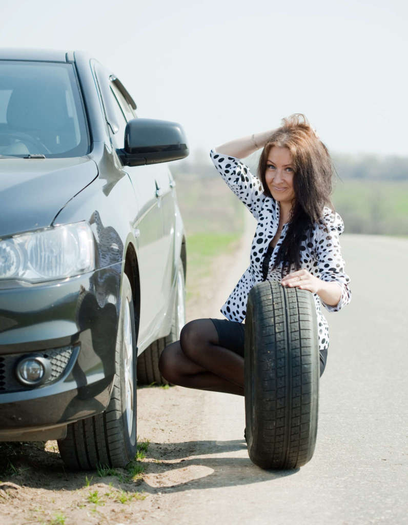 Woman changing car wheel