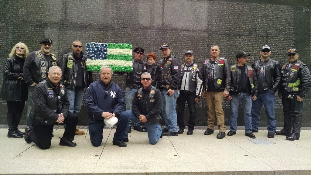 Many of the participants in the ride pose with the tribute in front of the wall with names of fallen police officers inscribed.